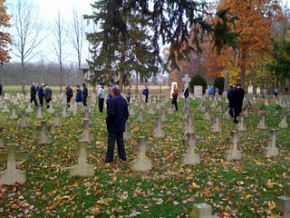 Holy Cross priests walk among the headstones