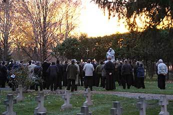 Holy Cross men praying at the Community Cemetery
