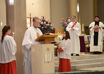 Deacon Dan Ponisicak, CSC watches as Fr Bill Wack, CSC proclaims the Gospel