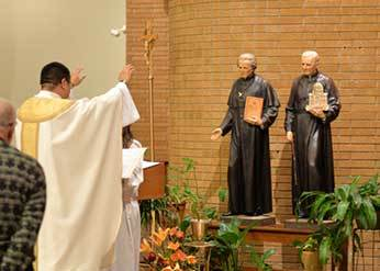 Fr Brian Ching, CSC blesses the new statues