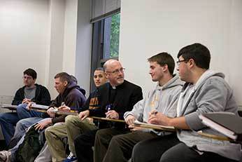 Fr Dan Issing, CSC with students at King's College