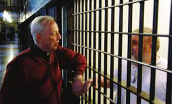 Fr Tom McNally, CSC visiting with an inmate
