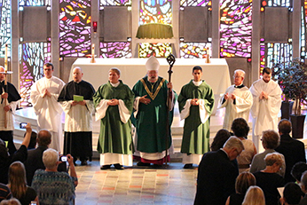 Bishop Jenky stands at the alter with the newly ordained deacons